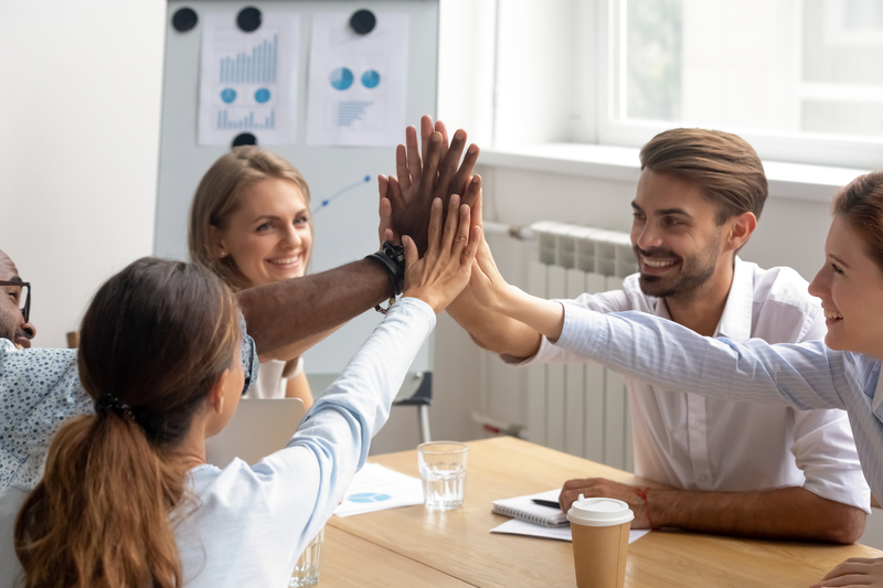 Happy motivated smiling diverse members of business team join hands palms together. Excited employees giving high five congratulate each other with successful teamwork, common goal achievement